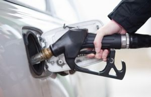 mobile brake service Alt Text: Close Up of a Hand Coming Out of a Black Sleeve Holding a Gas Pump While Fueling a White Car